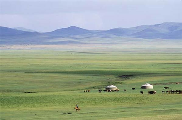a vast flat steppe with mountains in the distance