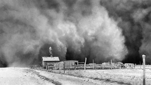 a huge cloud of dust engulfs a farm